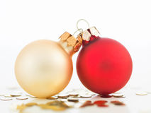 Colorful christmas globes joined together. Macro of two different colored christmas globes joined together with golden sequins arround them  on white Stock Images
