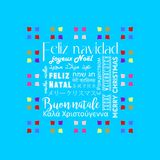 Colorful Christmas greeting card written in several languages like Spanish, sky blue background. 1 Royalty Free Stock Image