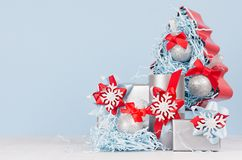 Colorful christmas home decoration - metallic gift boxes with bright red and blue silk ribbons and christmas tree on white wood. stock images