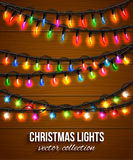 Colorful christmas light bulbs collection for. Celebratory design over wooden background. Shining Christmas background with blurred bokeh lights and place for Royalty Free Stock Photos