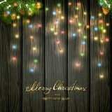 Colorful Christmas lights on black wooden background. Text Merry Christmas and Happy New Year with holiday decorations. Colorful Christmas lights with fir tree Royalty Free Stock Photography