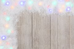 Colorful Christmas lights in snow corner border over white wood. Colorful Christmas lights in snow corner border, above view on a light gray wood background stock photos
