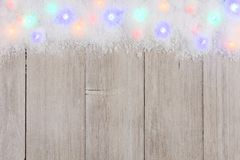 Colorful Christmas lights in snow top border over white wood. Colorful Christmas lights in snow top border, above view on a light gray wood background royalty free stock photos