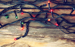 Colorful Christmas lights on wooden  rustic background. filtered image. Royalty Free Stock Images