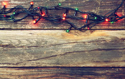 Colorful Christmas lights on wooden  rustic background. retro filtered image Royalty Free Stock Image