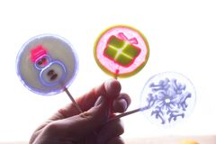 Christmas lollipops in hand. Colorful christmas lollipops with sticks in hand back lit Royalty Free Stock Photography