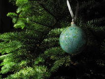 Colorful Christmas Ornament. A marbled blue and green Christmas ornament hangs from a Christmas tree Royalty Free Stock Photography