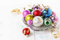 Colorful Christmas ornaments over white background. Colorful Christmas ornaments on a plate over white wooden background stock images
