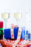 Colorful Christmas presents. Close up of colorful pile of Christmas presents with burning candle and two full glasses, white background stock photos