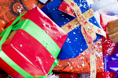 Colorful Christmas presents. Close up of colorful Christmas presents sprinkled with fake snow, festive scene royalty free stock photography