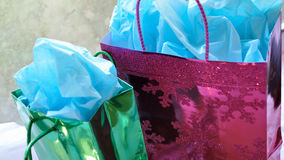 Colorful Christmas presents. Green and fuschia pink gift bags with happy blue tissue paper against a snowy winter window background stock photos