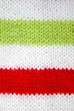 Colorful christmas red, white and green knitted pattern of Santa claus helper hat. stock photo
