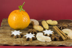 Colorful Christmas still life background. Colorful Christmas still life with a fresh clementine on a wooden board with peanuts, white star and vanilla crescent stock photo