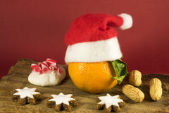 Colorful Christmas still life decoration. With star shaped cookies, nuts, meringue and a festive clementine with a red Santa Hat royalty free stock images
