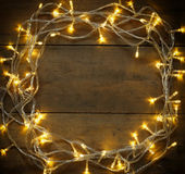 Colorful Christmas warm gold garland lights on wooden rustic background. filtered image Stock Images