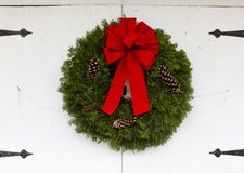Colorful Christmas wreath on old doors. A lone colorful Christmas wreath with a red ribbon and pine cones on old closed doors with wrought iron hinges stock photo
