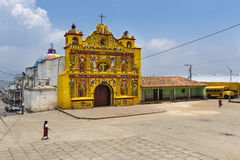 The colorful church of San Andres Xecul and three local Mayan woman walking on the street in Guatemala Royalty Free Stock Images