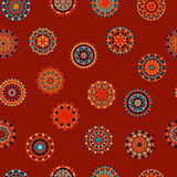 Colorful circle flower mandalas seamless pattern in orange and blue on red, vector. Background vector illustration