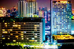 Colorful of city modern buildings night abstract background, dec. Orated with de-focus bokeh lights cities offices of reflecting building in Bangkok Thailand Royalty Free Stock Photos