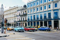 Colorful classic cars drive by old colorful buildings in Havana, Cuba. royalty free stock photo