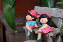 Colorful clay doll boy and girl sitting on small wooden chesterfield. The decoration of the small park Stock Photo