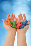 Colorful clay people in woman palm Stock Photography