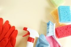 Colorful cleaning set for different surfaces in kitchen, bathroom and other rooms. Empty place for text or logo on pale yellow background. Cleaning service stock image