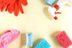 Colorful cleaning set for different surfaces in kitchen, bathroom and other rooms. Empty place for text or logo on pale yellow background. Cleaning service royalty free stock image