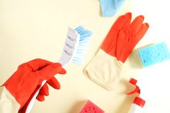 Colorful cleaning set for different surfaces in kitchen, bathroom and other rooms. Empty place for text or logo on pale yellow background. Cleaning service stock images