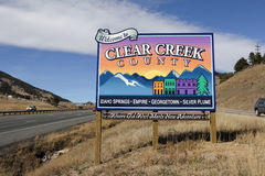 Colorful Clear Creek County Sign. Genesee, CO, USA - November 8, 2014: Westbound on I-70 towards Idaho Springs, Empire, Georgetown, SilverPlume and more towns Stock Photography