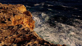 Colorful cliff line with deep blue ocean and breaking waves stock video footage