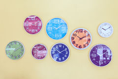 Colorful clocks decorated on the wall, vintage background. Royalty Free Stock Image