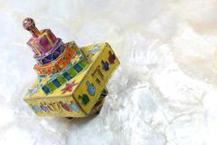 Colorful cloisonne Hanukkah dreidel on soft white background, space for text. Horizontal aspect Stock Photography