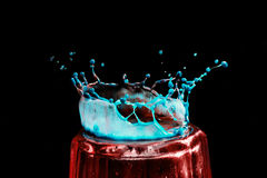 Colorful close-up a blue and red drop in the form of a crown is split on the glass Stock Photo