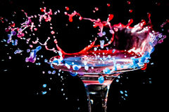 Colorful close-up a drop of red,blue and purple water is split on the glass in the form of a crown Royalty Free Stock Photo