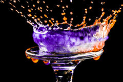 Colorful close-up a drop of violet and orange water is split on the glass in the form of a crown Stock Images