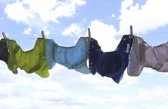 Cloth diapers hanging on clothes line. Colorful cloth diapers are hanging to dry on a clothes line with blue skies in the background Stock Photography