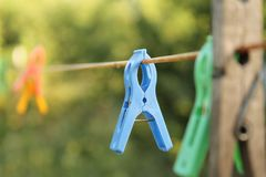 Colorful clothepins on a wire. Sunny summer day Stock Image