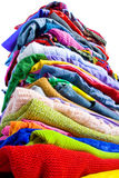 Colorful clothes. Tall pile of colorful clothes royalty free stock images