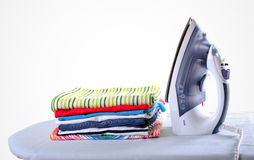 Colorful clothes and electric iron Stock Photos