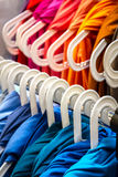 Colorful clothes on hangers Stock Photos