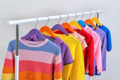 Colorful clothes hanging on wardrobe rack. Against light background stock images