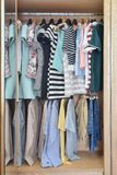 Colorful clothes hanging in wardrobe Royalty Free Stock Images