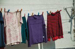 Colorful clothes hung to dry in front of building. With old whitewashed wall, in a sunny day Gouveia. A nice country town with gardens and captivating royalty free stock image
