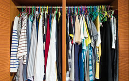 Colorful clothes men hanging in closet. Colorful clothes men hanging in wooden closet stock photos