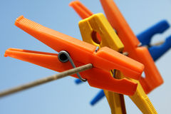 Colorful clothes pegs. Hanging in the line wire Stock Photos