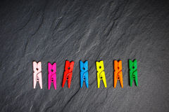 Colorful clothes pegs on black board Stock Photo