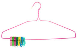 Colorful clothes Pegs clamped to pink hanger isolated Stock Image