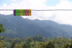 Colorful Clothes Pegs on a Line. Multicolored plastic clothes pegs pink purple yellow green hanging on line with hilly green rainforest background Royalty Free Stock Images
