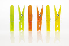 Colorful clothes pins. (green, orange, yellow, white background with reflection Stock Photos